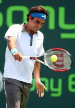 Roger Federer hits a one handed backhand at contact point.jpg