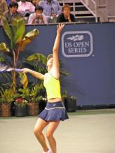Maria Sharapova serves, wearing yellow and purple.jpg