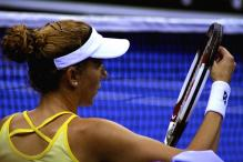 Seles checks the strings on her racquet.jpg