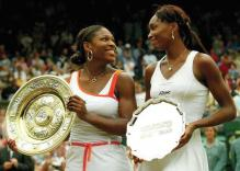 Venus Williams and Serena Williams holding their trophies at Wimbledon 2003.jpg