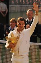 Roger Federer raises his arm while holding the 2009 Wimbledon trophy.jpg