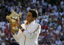 Roger Federer looks at his 2009 Wimbledon championship trophy.jpg