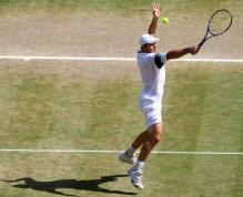 Andy Roddick goes for the high backhand volley during the 2009 Wimbledon finals.jpg