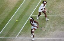 Venus Williams goes for a backhand on the run during Wimbledon 2009 doubles.jpg