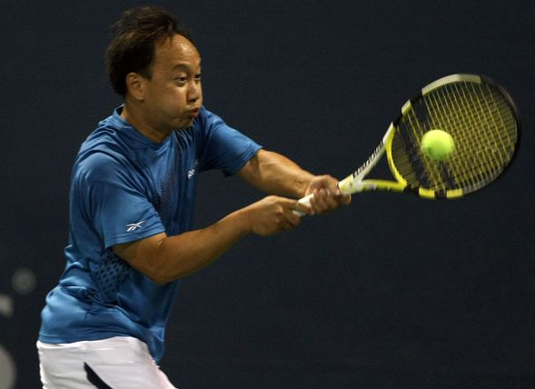 Michael Chang hits a backhand during his Legends match against Jim Courier.JPG