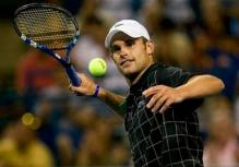 Andy Roddick hits a ball into the crowd after a win.JPG