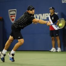 Andy Roddick stretches for a backhand block.JPG