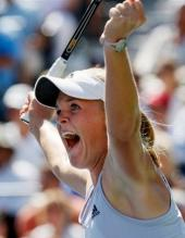 Melanie Oudin yells and raises her arms in celebration.JPG