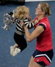 Kim Clijsters picks up her daughter while holding her 2009 US Open trophy.JPG