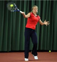 Kim Clijsters demonstrates hitting a high forehand.JPG