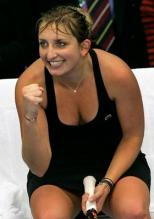 Timea Bacsinszky smiles and celebrates a point sitting down.JPG