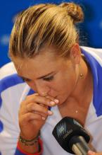 Maria Sharapova talks into the microphone in a white jacket.JPG