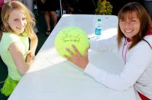 Vera Zvonareva smiles as she autographs a ball for a young fan.JPG