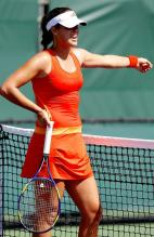 Ana Ivanovic in a right orange tennis dress guestures.JPG