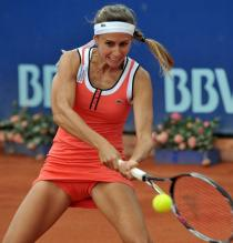 Gisela Dulko hits a 2 handed backhand in orange.JPG