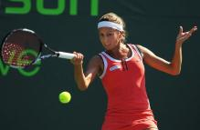 Gisela Dulko hits a topspin forehand in an orange dress.JPG