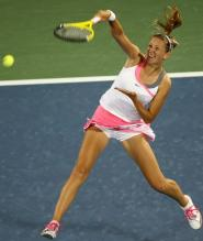 Victoria Azarenka hits an overhead smash in a white and pink Nike tennis dress.JPG