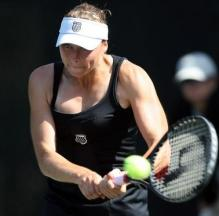 Vera Zvonareva in a black tennis outfit hits a 2 handed backhand.JPG