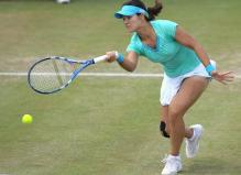 Li Na hits a top spin shot on a low ball on grass.JPG