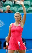 Victoria Azarenka in pink tennis dress raises her arm in acknowledgement.JPG