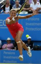 Victoria Azarenka hits a top spin shot on the run on grass 2010.JPG