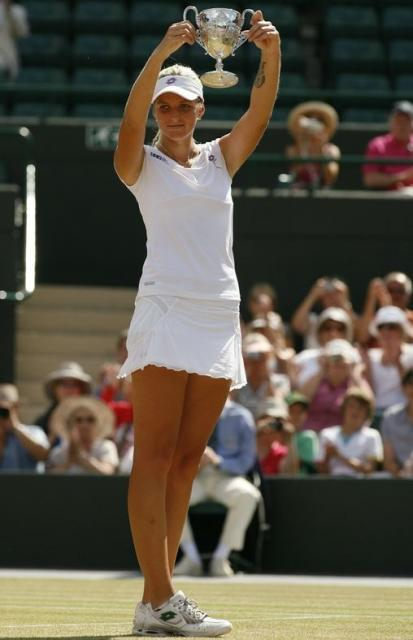 Kristyna Pliskova in white visor and tennis outfit holds her 2010 Wimbledon championship trophy.JPG