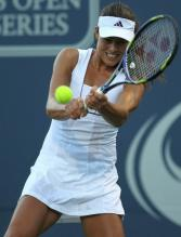 Ana Ivanovic in a white Adidas tennis dress hits a 2 handed backhand.JPG