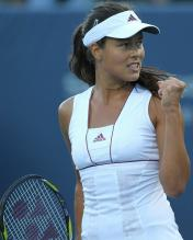 Ana Ivanovic in a white Adidas tennis dress celebrates a point.JPG