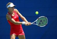 Maria Kirilenko in a red Adidas tennis dress hits a 2 handed backhand.JPG