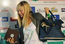 Sharapova smiles as she arrives as the French Open press conference.jpg