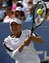 Vera Zvonareva hits a high ball with her 2 handed backhand at the 2010 US Open.JPG