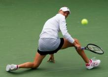 Vera Zvonareva looks behind her as she goes down to her knee to block back a ball.JPG
