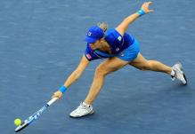 Kim Clijsters stretches to scoop up a low ball.JPG