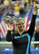Kim Clijsters gives the thumbs up in a black Fila jacket and raises the US Open championship trophy.JPG