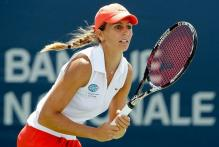 Gisela Dulko in a red tennis hat awaits to hit a groundstroke.JPG