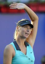 Maria Sharapova waves in a cyan Nike tennis dress and black Nike visors.JPG
