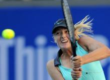 Maria Sharapova goes after a high backhand during the 2010 China Open.JPG