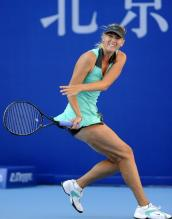 Maria Sharapova follows through on a defensive shot in Beijing 2010.JPG