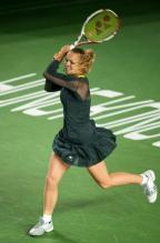 Caroline Wozniacki 2 handed follow through in a black tennis dress in Hong Kong 2011.JPG