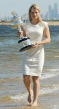 Kim Clijsters bare footed in white dress holding her 2011 Australian Open championship trophy at the beach.JPG