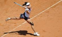 Li Na follows through on a two handed power backhand at the 2011 French Open.JPG