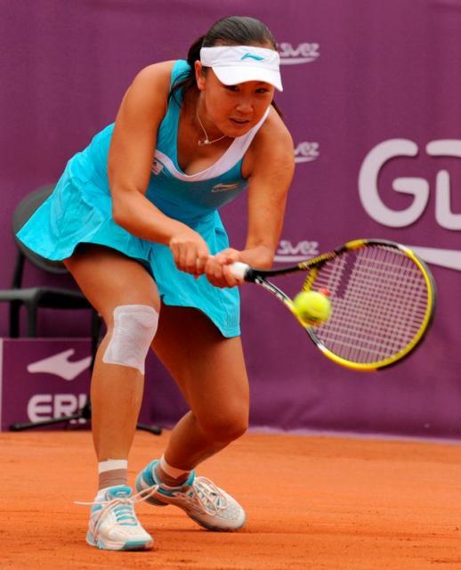 Peng Shuai in a cyan tennis dress hits a two handed shot ...