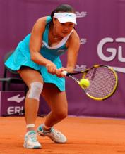 Peng Shuai in a cyan tennis dress hits a two handed shot at the French Open 2011.JPG