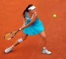 Peng Shuai bends her legs to hit a two handed shot on red clay.JPG
