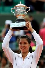Li Na in a white Nike tennis jacket holds her French Open 2011 champion trophy.JPG