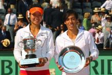 Li Na holds her 2011 French Open champion trophy with Sciavone holding the running up plate.JPG