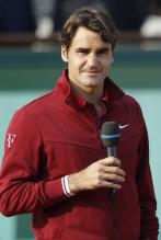 Roger Federer in a red Nike warmup jacket holds the microphone.JPG