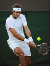 Juan Martin Del Potro bends his knees to hit a 2 handed backhand at 2011 Wimbledon.JPG