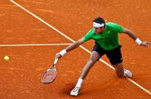 Juan Martin Del Potro slides on the red clay aftering hitting the backhand slice.JPG