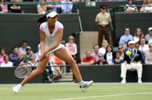 Laura Robson looks to scoop up a low ball with a 2 handed backhand at Wimbledon 2011.JPG